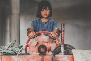 繊維業で働く児童労働の少女