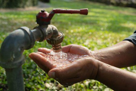 蛇口から水を汲む子供の写真