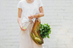 Plastic Free living: model with grocery bag and reusable water bottle