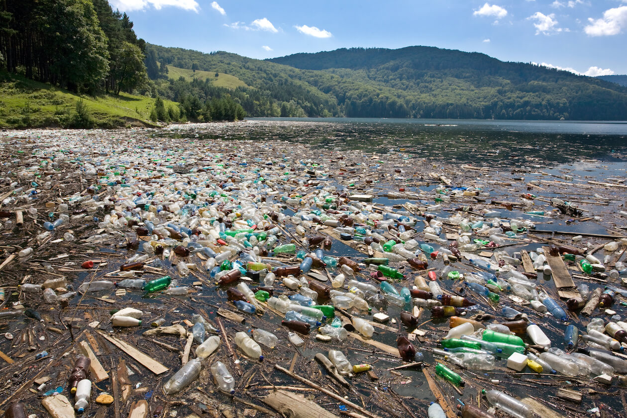A beach filled with plastic bottle and other waste = plastic pollution definition