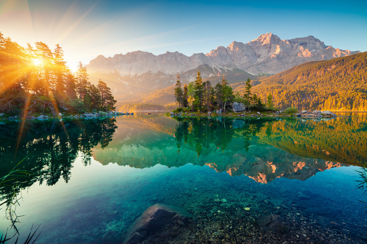 Beautiful photo of the nature with the sun setting and a lake with a clear refection of the trees and mountain
