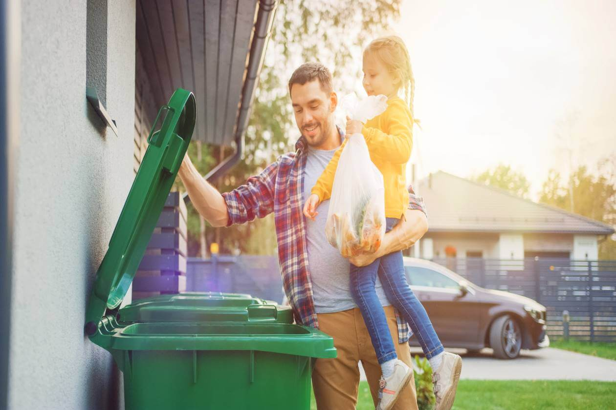 father and child throwing trash food waste
